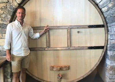 Provence Wine Tours - Brice, wine guide,in front of a cask in a Bandol winery
